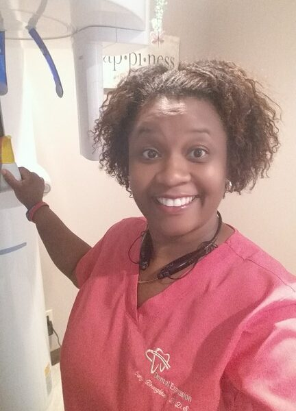 Dr. Cory smiling in her pink scrubs